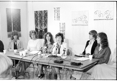 P123.005m.r.t Dixon Press Conference 1982:  (Left to Right) Fran Ledford, Chris Russell, Kathy Gilberd (MLTF, NLG), Diane Cooper (NOW/SD), Susan McGreivy (ACLU), Kim McAlister (CWSS), Eileen Bingle speaking at a press conference.