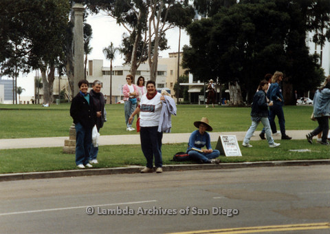 P024.454m.r.t 1990 San Diego Pride parade: Group of people across the street, person in center holds a purple jacket.