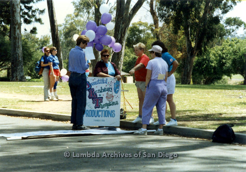 P024.423m.r.t 1990 San Diego Pride parade: Group of people including Judith McConnell in jeans (left) and Sally Hopkins in red shirt holding a Beautiful Lesbians Thespians sign