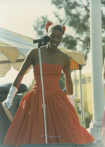 P104.152m.r.t San Diego Pride Festival 1989: Woman wearing red dress standing at microphone.
