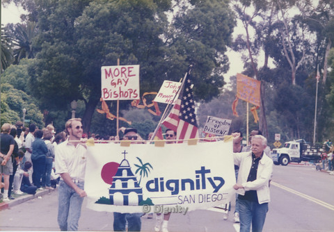 "P104.113m.r.t Dignity San Diego at San Diego Pride Parade 1989: Bruce Neveu (on left) and another man  lead march while holding ""Dignity San Diego"" banner."