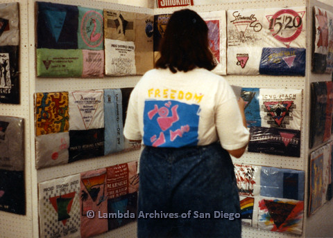 P024.463m.r.t 1990 San Diego Pride festival: Woman looking at pride t-shirt display in the Gay and Lesbian Archives booth
