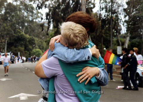 P024.504m.r.t 1989 San Diego Pride: Marghi Kilmer in a jean jacket hugging Sally Hopkins in a lavender shirt