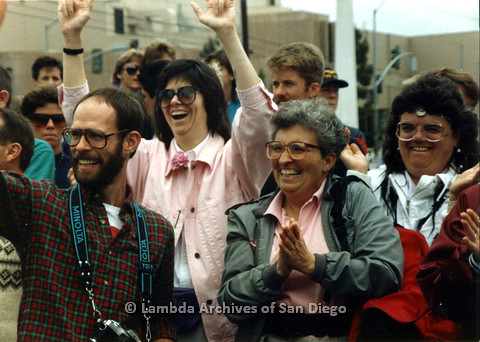 P024.489m.r.t 1990 San Diego Pride Parade: (Left to right) Unknown male with glasses, unknown woman with hands in the air, Cait Casey  with hands together, and Michael Ann smiling in white.