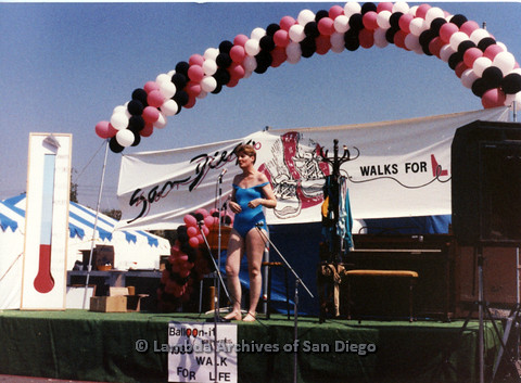 "P024.202m.r.t Judith McConnell standing on stage with sign ""Balloon-it supports 1989 Walk for Life"""