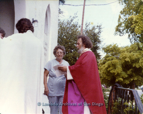 P110.018m.r.t Metropolitan Community Church: Joseph Gilbert wearing red robes showing paper to mother Lovedy Gilbert outside St John's Lutheran Church.