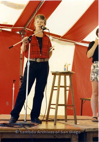 P024.251m.r.t Judy Grahn (left) standing at microphone beside ASL translator (far right).