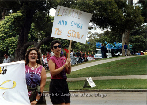 "P024.432m.r.t 1990 San Diego Pride Parade: Two women marching and holding signs, sign on left reads ""Lesbiate and smash the state!"""