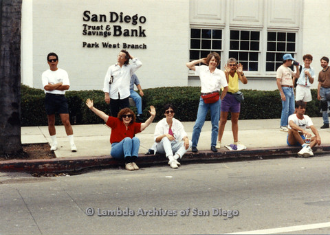 """P024.466m.r.t 1990 San Diego Pride Parade: People sitting and standing on the sidewalk in front of buildings that reads, """"San Diego Trust and Savings Bank, Park West Branch"""""""