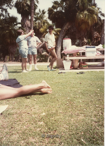 P104.054m.r.t Dignity Picnic 4th of July: Picture of man showing off thigh, while two people in background converse