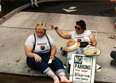 "P024.518m.r.t 1990 San Diego Pride Parade: Two women wearing ""Leather and Lace"" shirts sitting on the sidewalk"