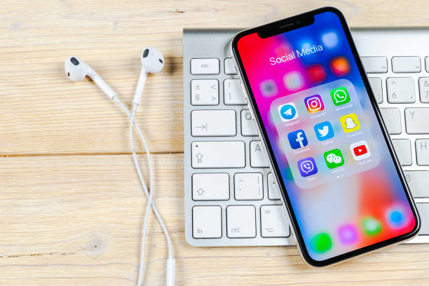 Apple iPhone X on office desk with icons of social media f