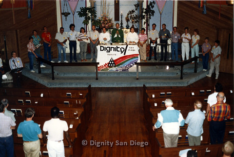 "P103.013m.r.t Dignity San Diego: church congregation with banner  ""Dignity / San Diego honors: Neal, Frank, Tom, Cesar"""