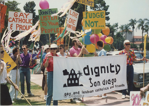 "P104.112m.r.t Dignity San Diego at San Diego Pride Parade: Bruce Neveu (in pink polo) and other men and women standing with signs behind a ""Dignity San Diego: gay and lesbian catholics and friends"" banner at Pride San Diego."