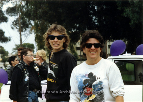 P024.493m.r.t 1990 San Diego Pride Parade: Two people in sunglasses and sweaters smiling