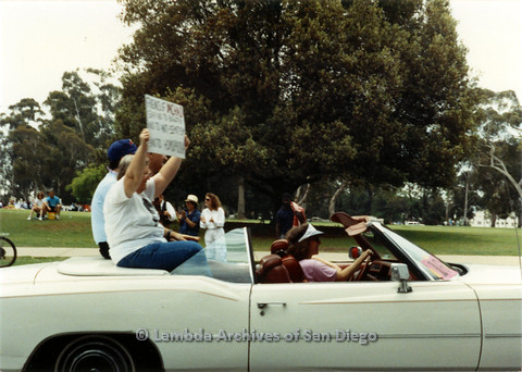 P024.453m.r.t 1990 San Diego Pride parade:Three people on back seat of a convertible, one holds a sign. A woman in pink drives.