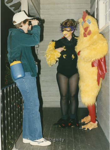 P104.104m.r.t Dignity San Diego: Person in chicken suit posing with woman in feathered leotard for another camera