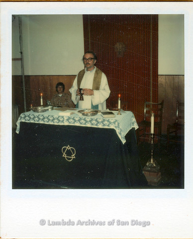 P110.014m.r.t Metropolitan Community Church: Man in robe holding chalice standing behind table.