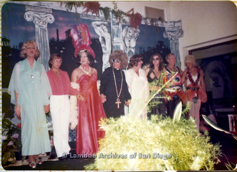 P110.020m.r.t Metropolitan Community Church: Group of men in diverse drag outfits standing before colonnade backdrop.
