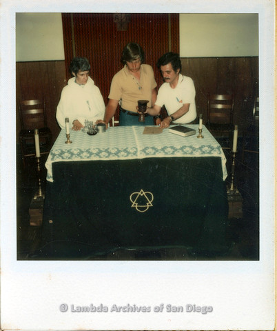 P110.007m.r.t Metropolitan Community Church: Three people standing behind table with several candles.