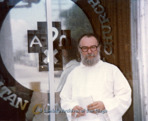 P110.049m.r.t Metropolitan Community Church: Joseph Gilbert holding paper while standing in front of glass with Metropolitan Community Church logo.