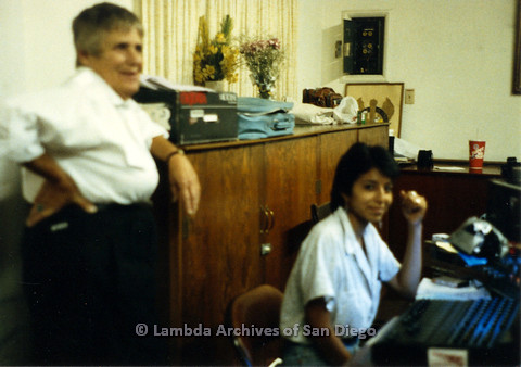 P024.159m.r.t  Kate Rosenblatt (left) leaning on cabinet with Viviana (Cosette) Enrique working a sound board