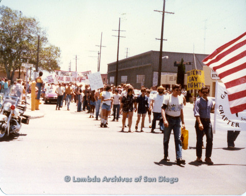 "P109.023m.r.t San Diego Pride Parade 1978: In the midst of parade with prominent USA flag and ""Defend Gay Rights"" sign."