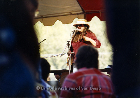 P024.267m.r.t Woman in red jacket on day stage behind microphone.