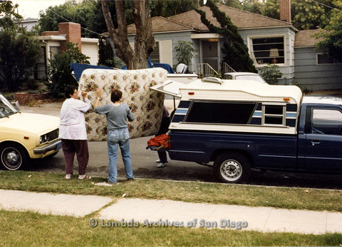 P024.347m.r.t Moving Sheila Shanahan and Nancy Groswich: Several women loading a mattress in to a truck.