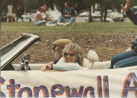 P104.120m.r.t San Diego Pride Parade: Elderly pair in car with STONEWALL written on side.