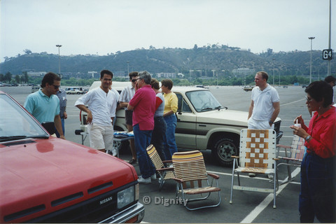 P104.075m.r.t Dignity San Diego: Men and women standingaround folding chairs in a parking lot