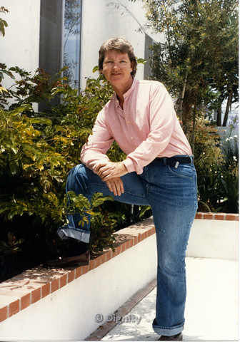 P104.039m.r.t Dignity San Diego: Person in pink polo with leg raised on a planter box