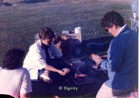 P104.026m.r.t Dignity San Diego: Women crowding around tray of hotdogs and burgers