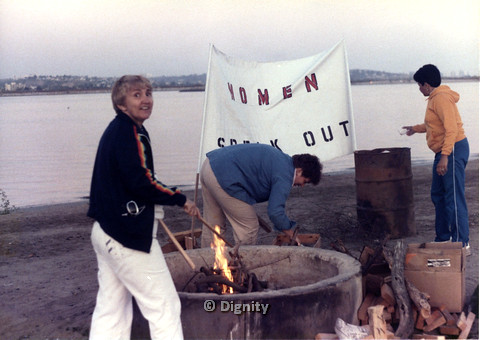 "P104.023m.r.t Dignity San Diego: Three women at bonfire on beach, ""WOMEN SPEAK OUT"" sign in background"