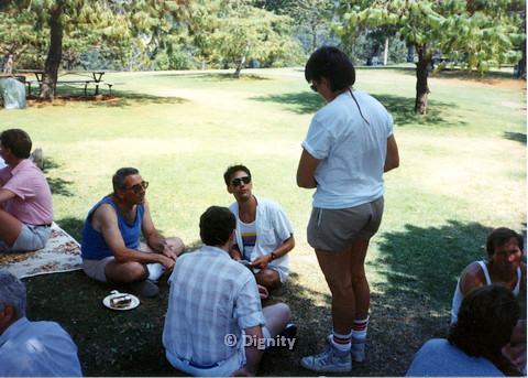 P104.055m.r.t Dignity Picnic 4th of July: Standing person talking to sitting men at the park