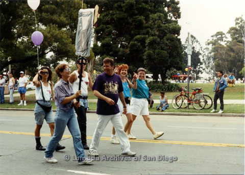 P024.419m.r.t 1990 San Diego Pride parade: People marching in parade, Heather Dawn Artemis (red hair) waves