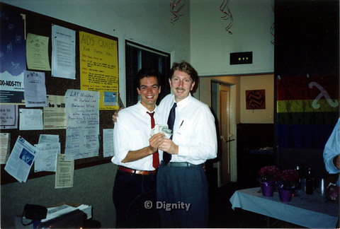 P104.196m.r.t Dignity San Diego: Two men in dress shirts and ties in front of a bulletin board hold cash while in a half embrace with a table and lambda marked rainbow flag in background.