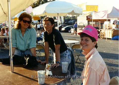 P024.512m.r.t 1989 San Diego Pride festival: (Left to right) Two unknown women and Judith McConnell at a table.
