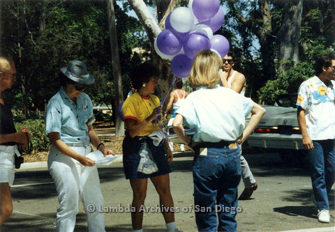 P024.476m.r.t 1990 San Diego Pride Parade: People standing  on asphalt, woman in yellow shirt holds purple and white balloons