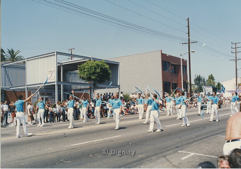 P104.122m.r.t San Diego Men's Chorus at San Diego Pride Parade: San Diego Men's Chorus wearing blue shirts and twirling blue ribbons in parade.
