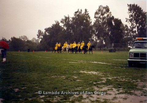 P024.548m.r.t  People in yellow raincoats riding horses