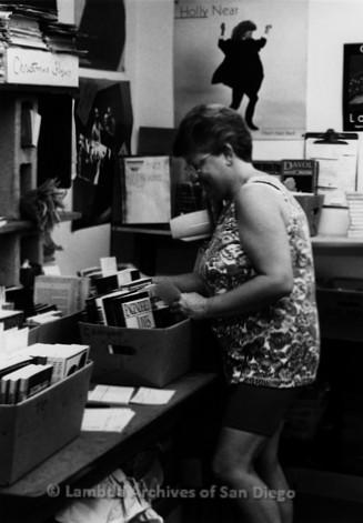 P167.094m.r.t Paradigm Women's Bookstore: Woman organizing books in back room