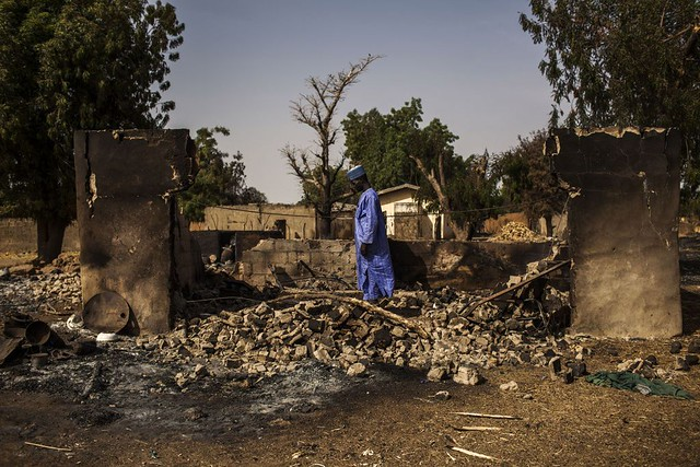 Un-nigeriano-camina-sobre-las-ruinas-de-su-casa-después-de-que-Boko-Haram-haya-arrasadosu-poblado-en-el-estado-de-Borno.-Nigeria-2014-Diego-Ibarra