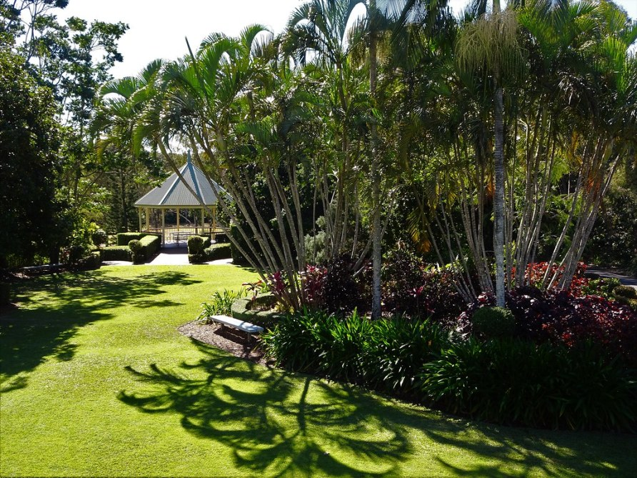 Bundaberg. Gardens around Fairymead sugar plantation homestead. The gazebo and palms with the lake beyond.