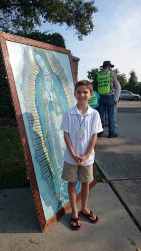 Max praying on the sidewalk with an image of Our Lady of Guadalupe. Photo couresty of the Volanski family.