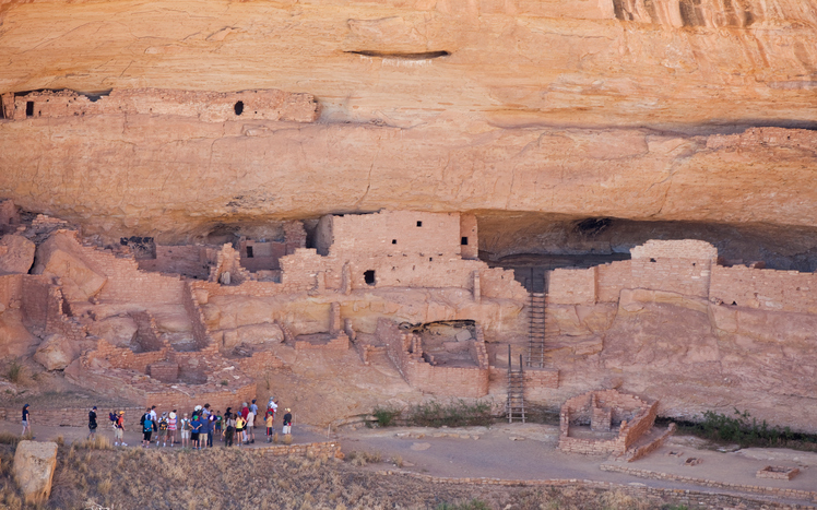 """Mesa Verde, Colorado, United States - June 12, 2012. Park Ranger guiding tourists through Long House Ruins in Mesa Verde National Park, Colorado. The Anasazi inhabited the area between 600 to 1300 and the ruins left behind draw many tourists every year."""