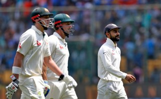 India's captain Virat Kohli, right, walks back with Australia's batsmen Matt Renshaw, left, and Shaun Marsh for the lunch break during the second day of their second test cricket match in Bangalore, India, Sunday, March 5, 2017. (AP Photo/Aijaz Rahi)