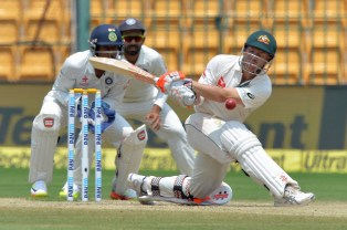 Australian batsman David Warner watches as the ball hits his pads as he is dismissed for leg before wicket during the fourth day of the second Test match between India and Australia at The M. Chinnaswamy Stadium in Bangalore on March 7, 2017. / AFP PHOTO / Manjunath KIRAN / ----IMAGE RESTRICTED TO EDITORIAL USE - STRICTLY NO COMMERCIAL USE----- / GETTYOUT