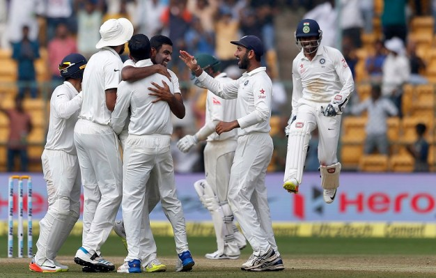 India's Ravichandran Ashwin, center without cap facing camera, celebrates with teammates the dismissal of Australia's Peter Handscomb during the fourth day of their second test cricket match in Bangalore, India, Tuesday, March 7, 2017. (AP Photo/Aijaz Rahi)