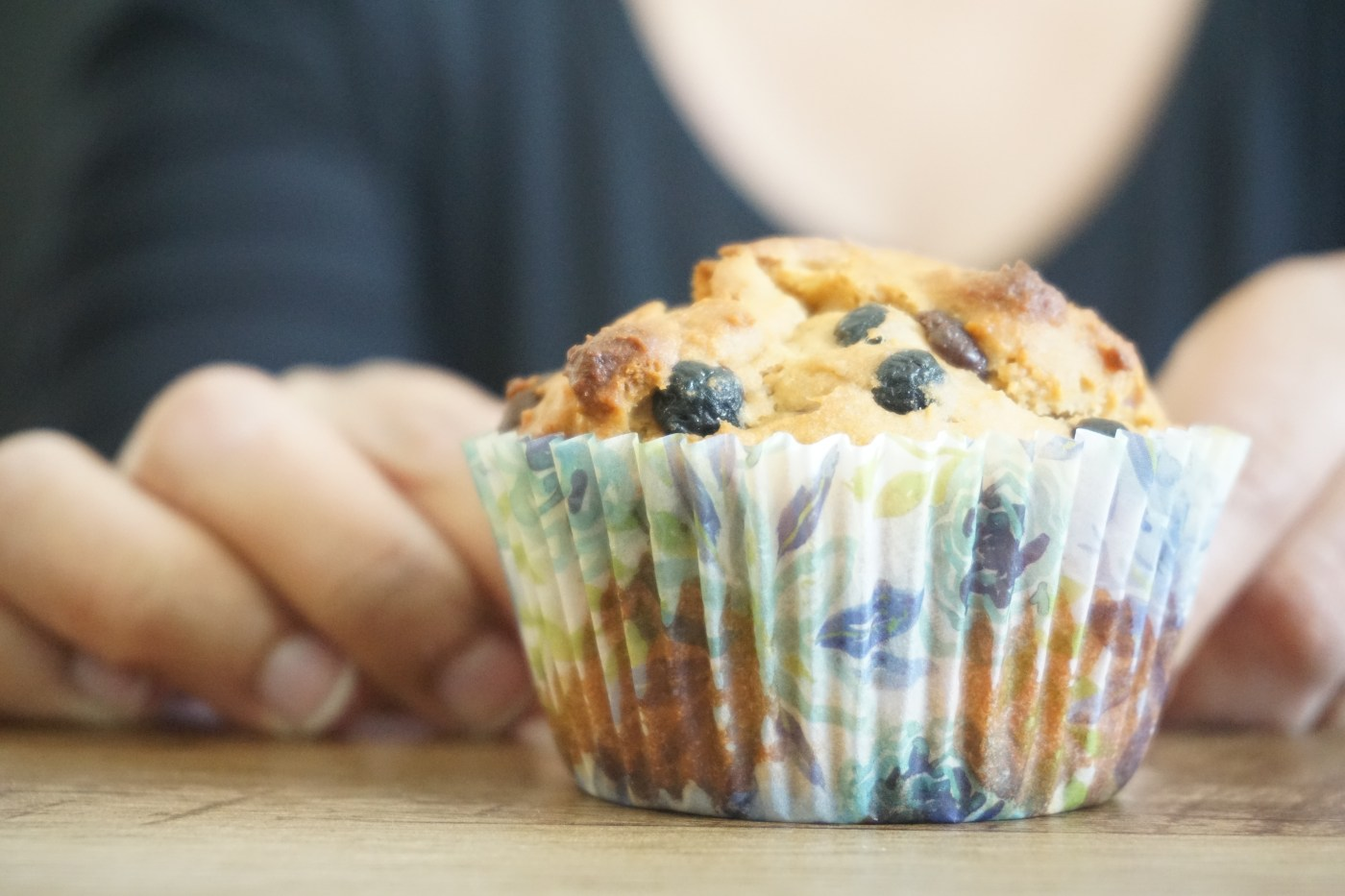 hands holding muffin with liner